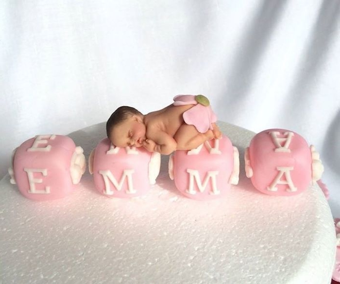 emma spelled out by pink alphabet cubes, with white letters, made from fondant, and decorated with a realistic sleeping baby figurine, in a pink flower nappie, baby shower cake toppers girl