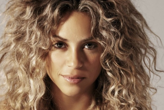 haircuts for curly hair, shakira seen in close up, with glossy beige lipstick, and discrete make up, long and voluminous, messy and feathery blonde hair, with darker roots
