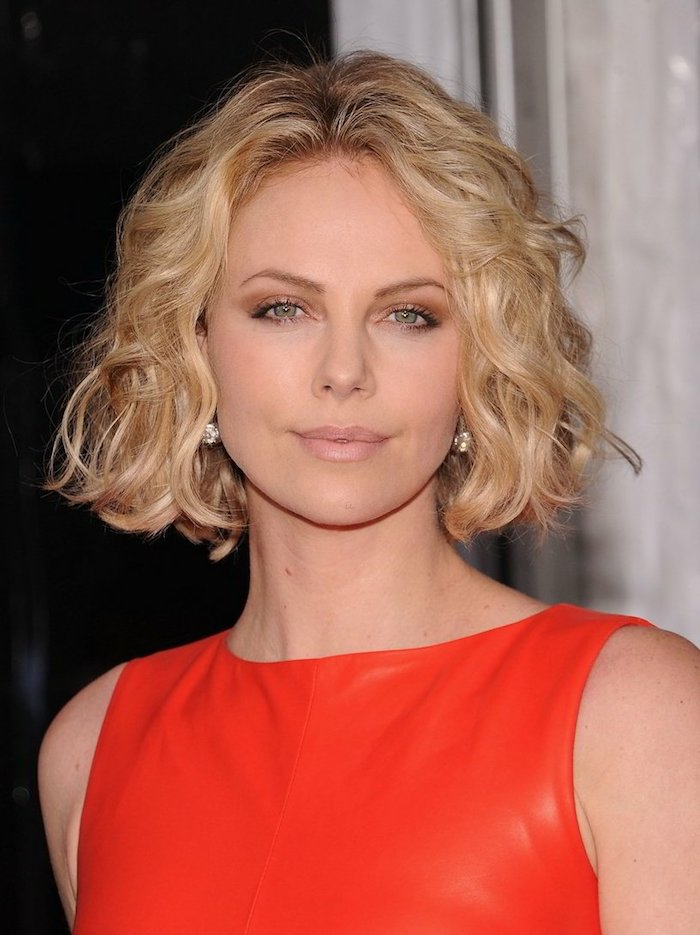 leather-like glossy red dress, worn by charlize theron, blonde short curly bob, with middle part, nude pink lipstick, and subtle eye make up