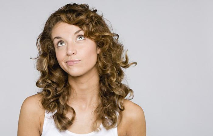 funny thinking face, made by woman, wearing a white tank top, hairstyles for curly hair, medium long brunette curls, with side part, and dark blonde highlights
