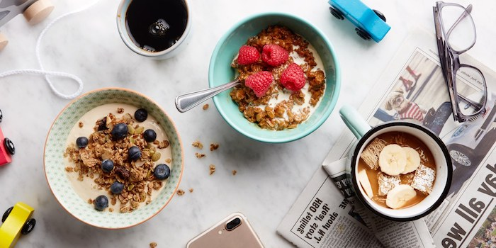 muesli and cereals, with milk and different fruit toppings, blueberries raspberries and bananas, in two bowls and a mug, on a table with lots of objects, healthy breakfast ideas