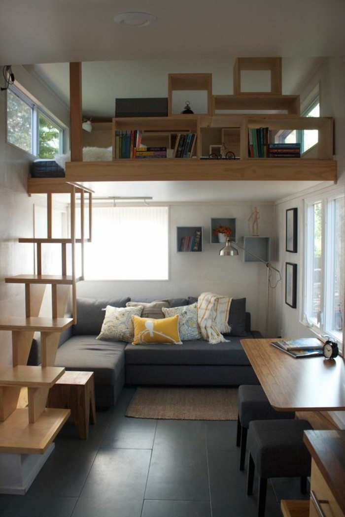 compact space with black tiled floor, and a second story with bookshelves, simple living room designs, grey corner sofa, with several cushions