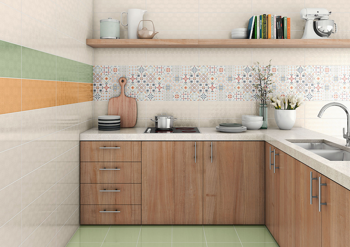 various kitchen utensils, off-white counter tops, and pale brown cabinets, in a room with an arabesque backsplash, and tiled walls