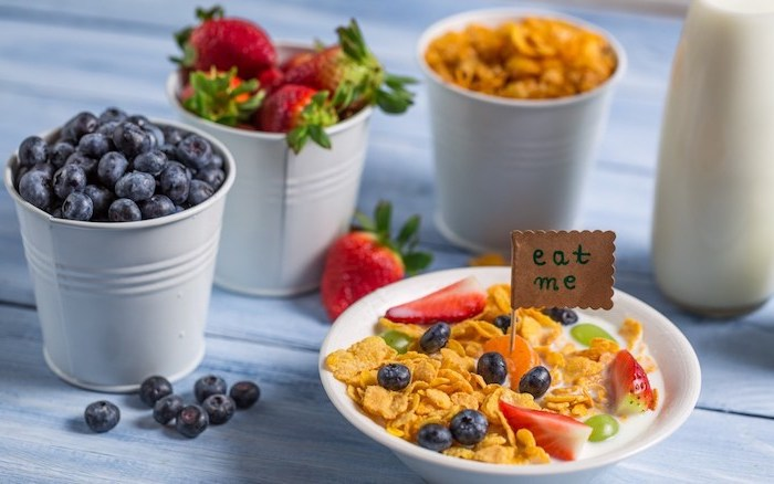 cereal with milk, covered with fruit, blueberries and grapes, sliced strawberries and clementines, healthy low calorie breakfast, berries and cornflakes in small pots nearby