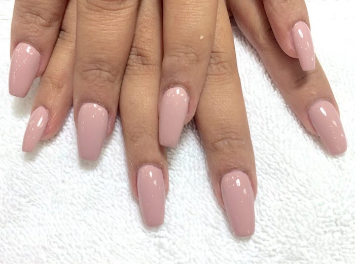 fabric in white, with towel-like texture, under eight tan fingers, oval nails with square tips, painted in nude pink nail polish