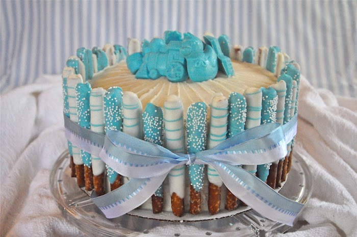 train and duckling, and other shapes, made from pale blue fondant, and placed on a creamy cake, lined with pretzel sticks, dipped in light blue and white frosting