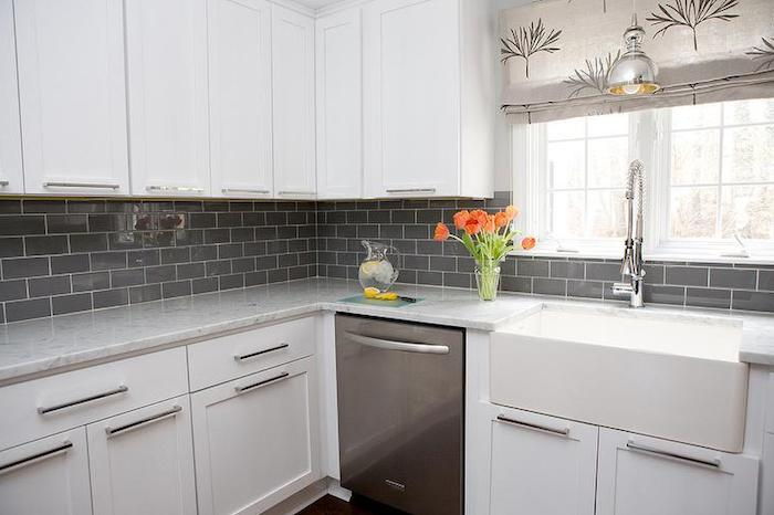 grey subway tile pattern, on the wall of a kitchen, with smooth and white, modern sink and matching cabinets, clear vase with tulips