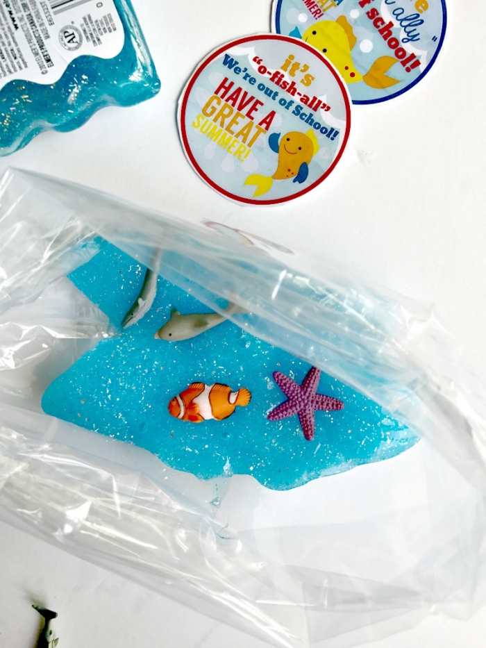 fish made form plastic, and some glitter, decorating a turquoise piece of goo, how to make slime with shaving cream, placed inside a clear plastic bag