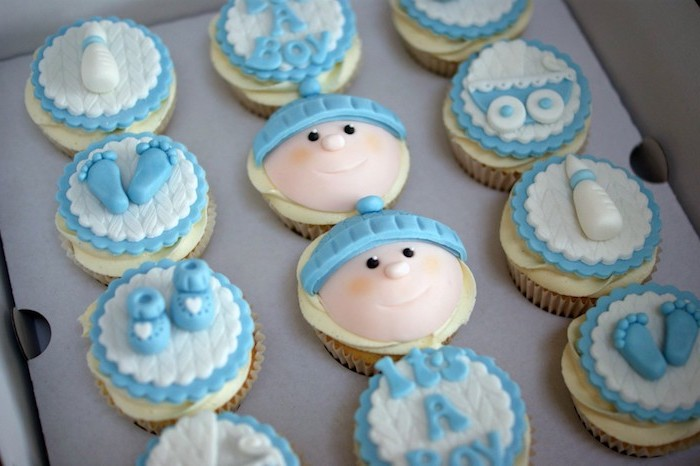 dozen of cupcakes in a cardboard box, pale yellow frosting, and blue and white fondant decorations, little feet and shoes, baby head and bottle, baby shower cakes for boys, pram and the words it's a boy