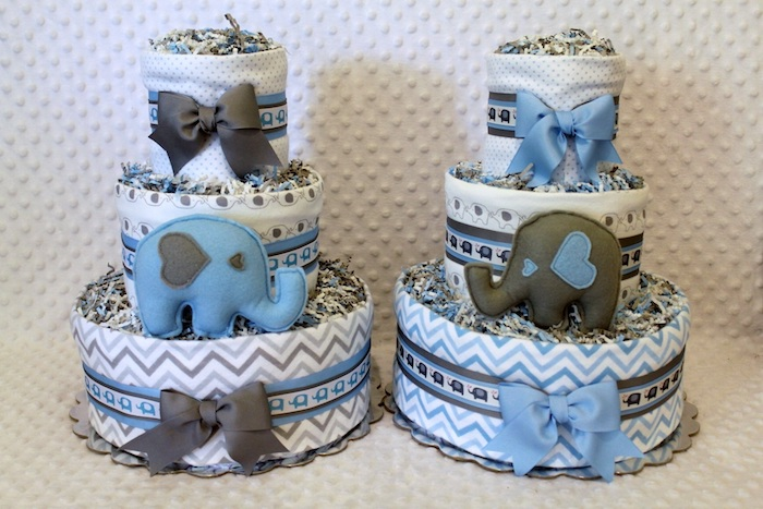 diaper cakes in white, with blue and grey patterns and bows, and two elephant stuffed toys, in blue and dark grey, elephant baby shower cake, a set of two