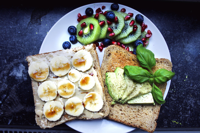 slices of bread, one with peanut butter, banana slices and honey, and one with avocado and basil, breakfast menu ideas, on a plate with kiwi slices, pomegranate seeds and blueberries