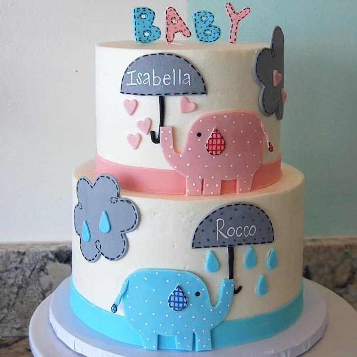 clouds and raindrops, decorating a white, two-layer cake, elephant baby shower cake, featuring a pink and a blue elephant, holding grey umbrellas, with the names rocco and isabella