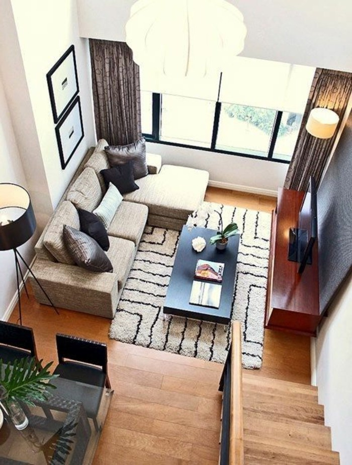high angle image, showing a bright room, with a beige corner sofa, a patterned beige and brown rug, and wooden laminate floor, simple living room designs, tv on a dark brown stand