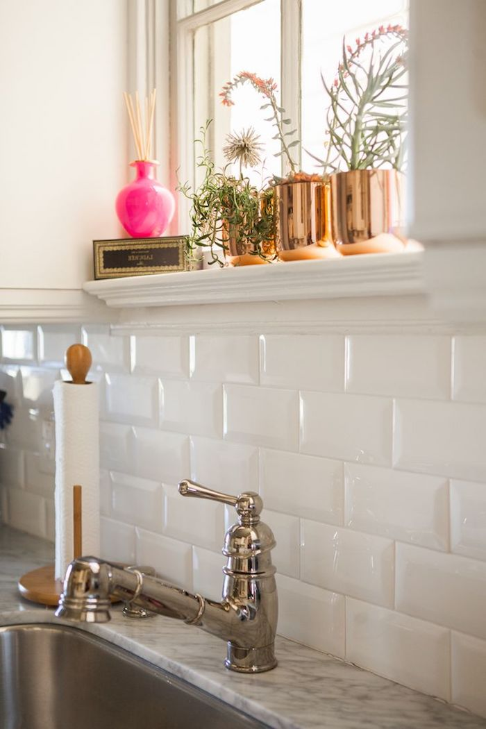 faucet in a vintage style, next to a sink and a marble counter top, white subway tile back splash, three brass planters with flowers