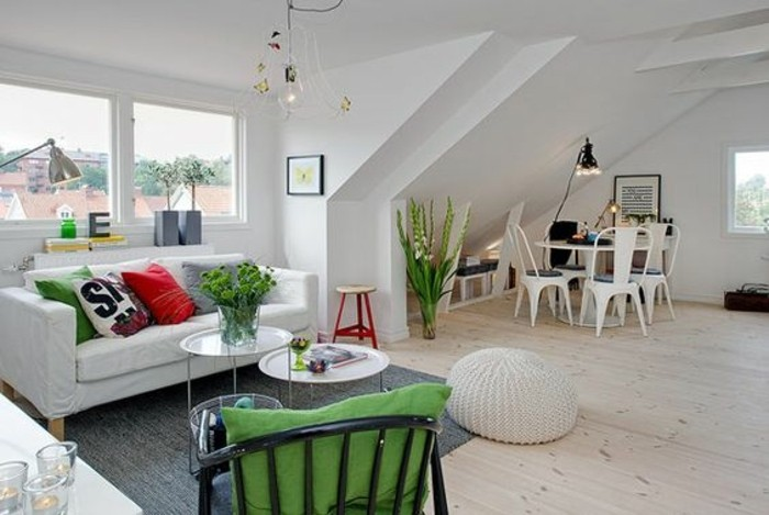 green cushions and potted plants, inside a spacious white studio, with pale beige laminate floor, white sofa and two coffee tables, and a dining area, home decor inspiration