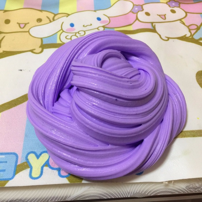 purple piece of goop, twisted into a roundish shape, how to make fluffy slime, placed on a colorful surface, with pastel colors, and cartoon drawings