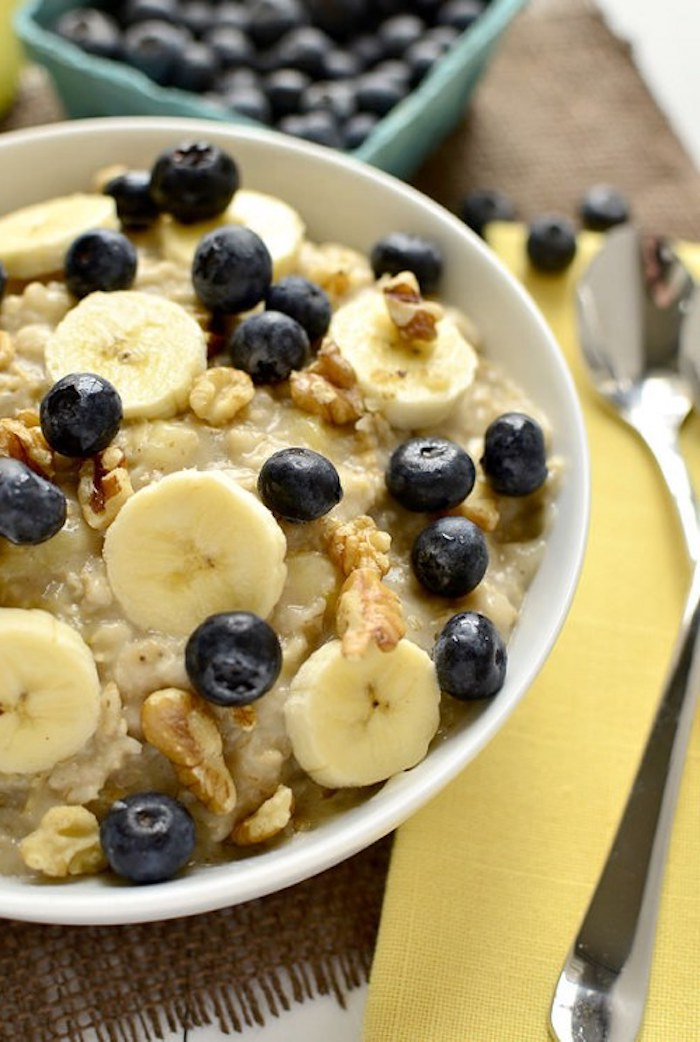 porridge topped with banana slices, blueberries and walnuts, inside a white bowl, next to a yellow paper napkin, with metal cutlery