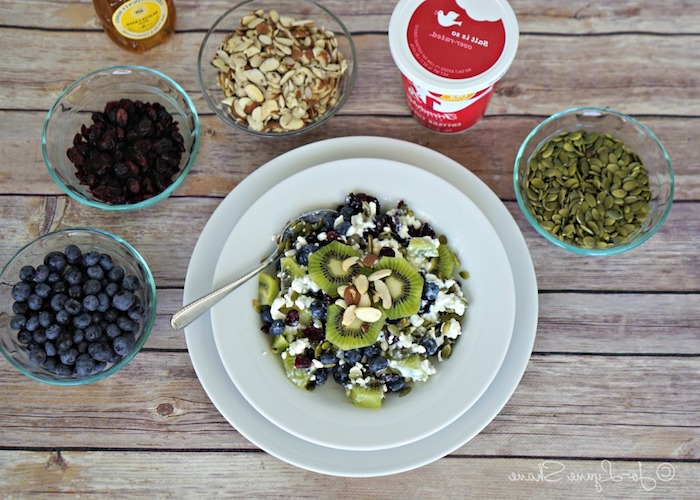 raisins and blueberries, cashews and pumpkin seeds, yoghurt and honey, near a plate containing fruit salad, with kiwi slices, healthy low calorie breakfast