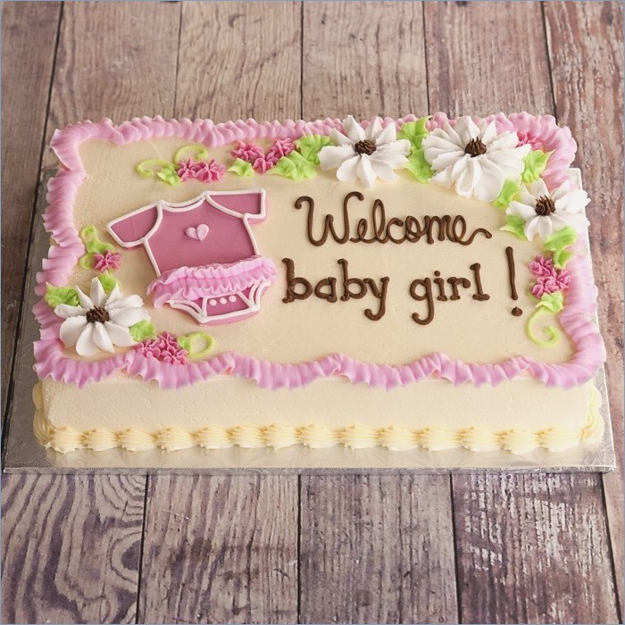 welcome baby girl, written with brown frosting, on a rectangular cake, baby shower cakes for girls, decorated with a little pink onesie, and white and pink flowers