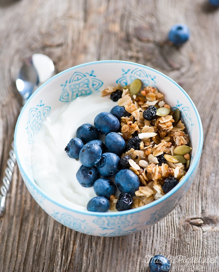 pumpkin seeds and raisins, granola and blueberries, on the side of a bowl, containing creamy yoghurt, best breakfast for weight loss, on a wooden surface