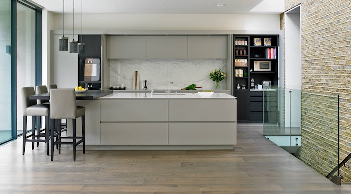 marble-like pale grey, and white kitchen backsplash, in a room with light grey cabinets, black shelves and a laminate floor