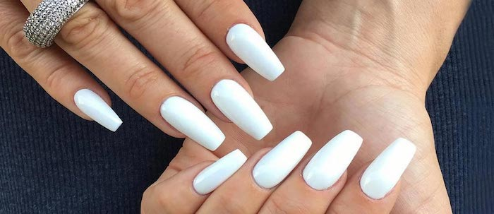 pure white nail polish, on two hands with four visible nails, one hand has a chunky, encrusted silver ring on its ring finger, coffin nails