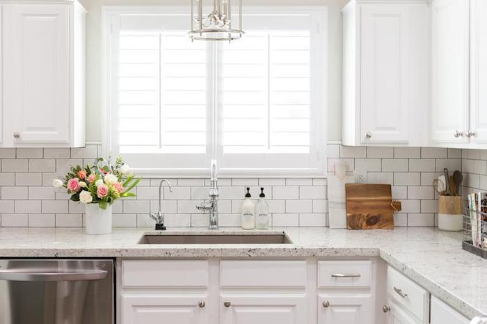 bouquet in a white vase, placed on a marble counter top, near two windows, white subway tile pattern, and matching white cabinets