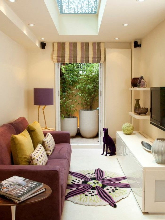 purple sofa with two sets of matching cushions, inside a narrow room, couches for small living rooms, a round rug and a small coffee table