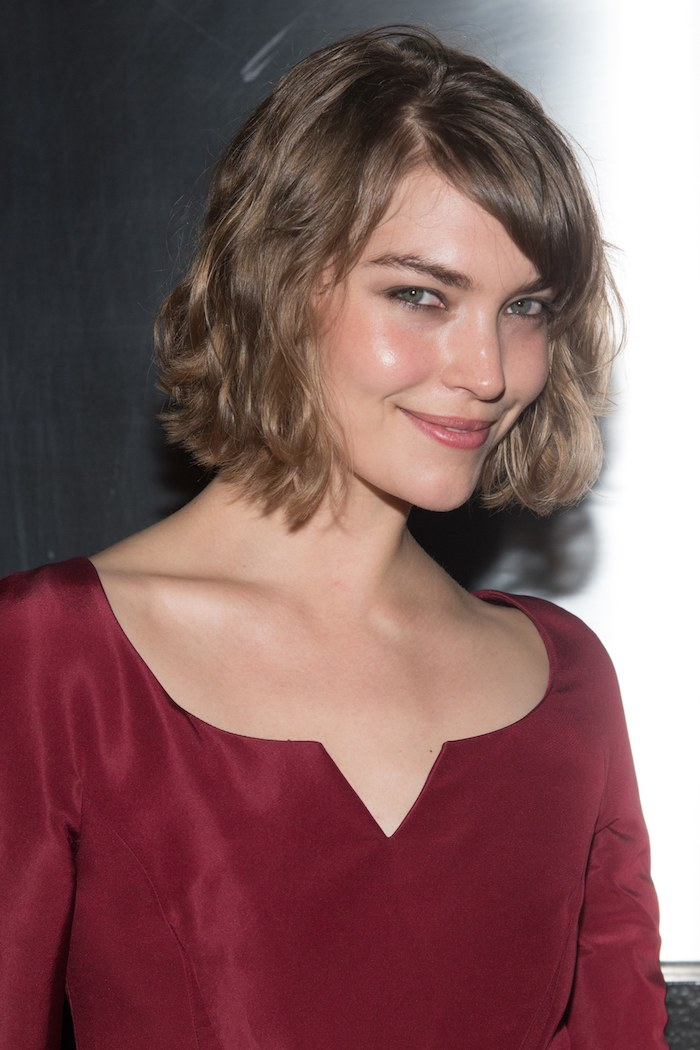 short hairstyles for fine hair, smiling brunette woman, wearing a long-sleeved silky wine red blouse, with wavy chestnut brown bob, and a side part