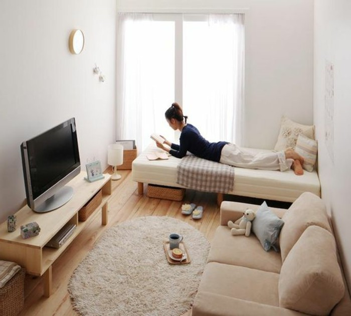 brunette young woman, lying on a narrow white bed, inside a small room with white walls, and a window, couches for small living rooms, beige sofa opposite a tv, on a wooden stand
