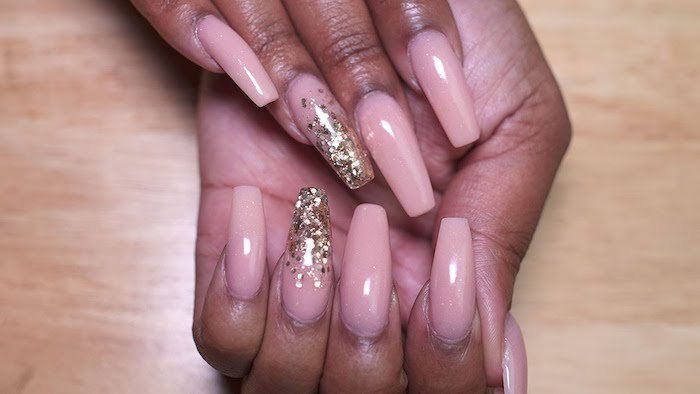 ballerina nail shape, painted in nude pink, and decorated with flakes of golden glitter, on brown hands, resting on a light wooden surface