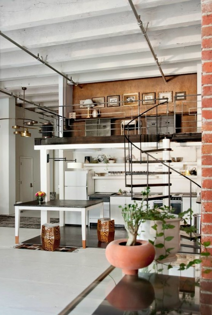 industrial style studio flat, with a winding wrought iron staircase, containing a large black and white table, home decor inspiration, a kitchenette and some shelves