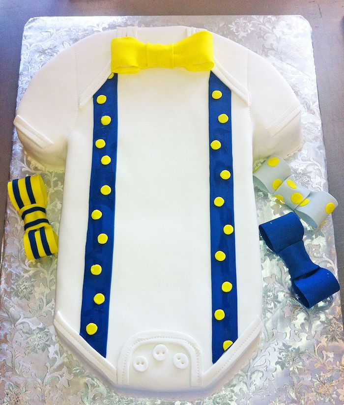 bowties in yellow and dark blue, plain and patterned, decorating a onesie cake in white, with blue suspenders, and three white buttons