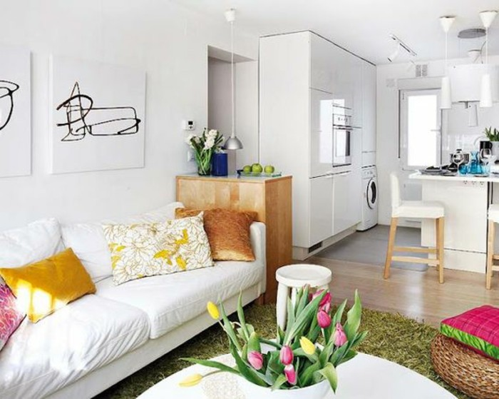 room design, white walls and a beige laminate floor, in a studio with a white couch, round coffee table, and a fluffy green rug