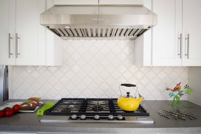 arabesque tile backsplash, in off-white, on the wall of a kitchen, with white cabinets, and a grey counter top, with inbuilt hob