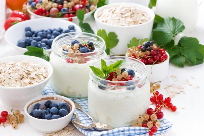 berries of different kinds, topping two small glass jars, filled with yoghurt, healthy low calorie breakfast, dishes with rolled oats, blueberries and other fruit