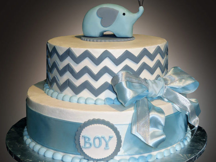 elephant baby shower cake, white with two layers, decorated with shiny blue ribbons, and blue zig-zag shapes, the word boy, written with blue frosting