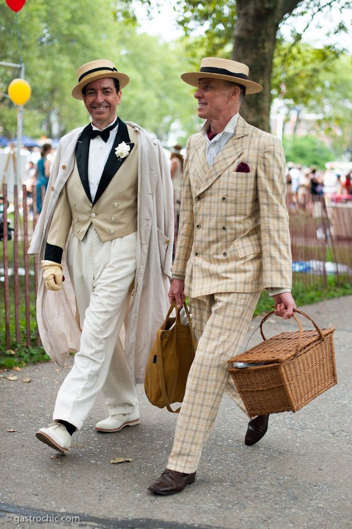 roaring 20s fashion, two smiling men, wearing cream and white 1920s suits, and falttop hats, walking on a street, one of them is holding a picnic basket