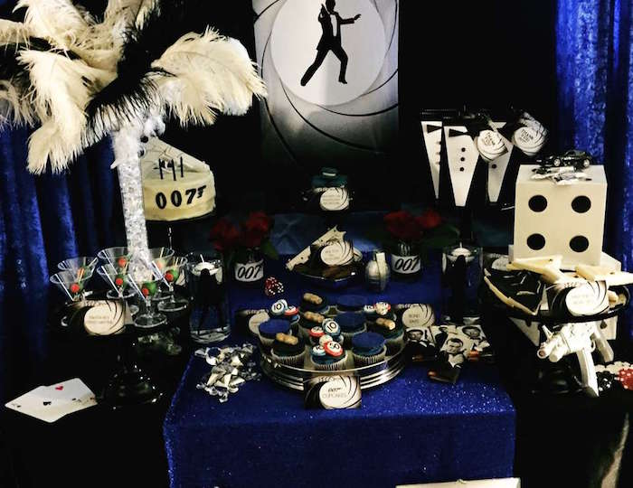 martini glasses and little tuxedo party favors, ostrich feather decoration, a large playing dice, and cupcakes with gambling chips, 60th birthday party ideas, inspired by agent 007