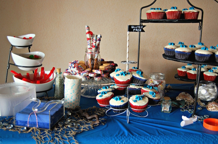 gummy bears and cupcakes, and various other sweets, on a table with a blue tablecloth, 60th birthday party ideas for men, fishing inspired table setup