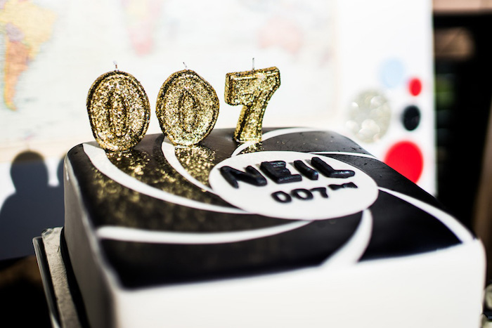 3 candles shaped like the numbers 007, in a sparkly gold color, on a black and white cake, 60th birthday party ideas, James Bond inspired decoration