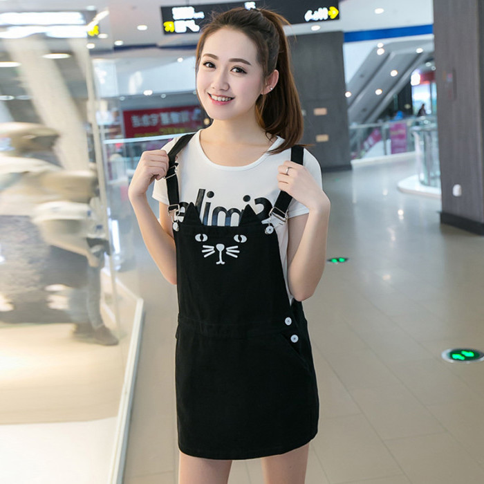 cat face printed in white, on a short black pinafore dress, worn by a smiling east asian girl, with a white t-shirt