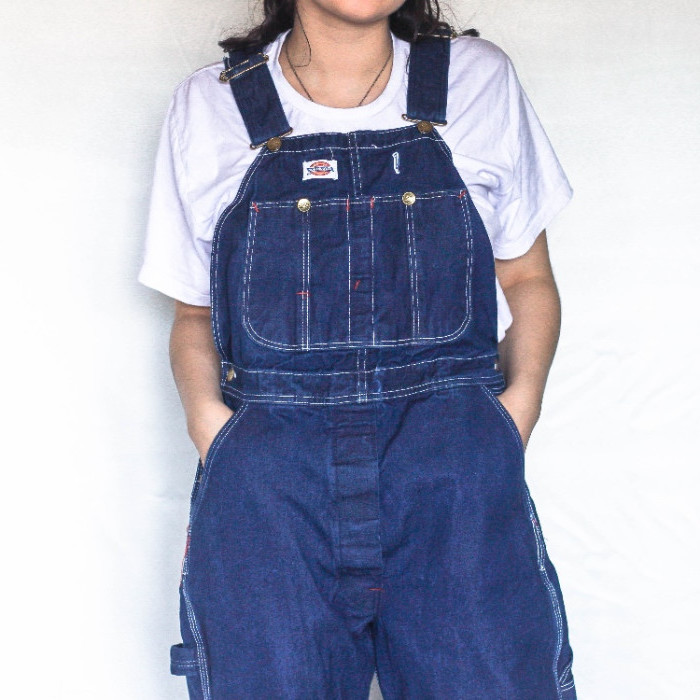 baggy retro denim overalls, in indigo blue, worn over a plain white t-shirt, by a dark-haired woman, 90s themed outfits