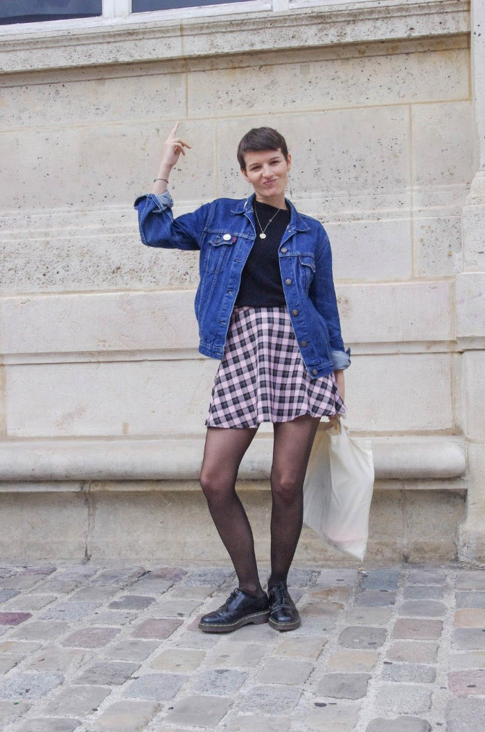 pixie cut worn by young brunette woman, in a pale pink and black plaid skirt, 90s inspired outfits, black top and an inky blue denim jacket