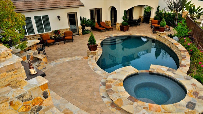 small inground pools, a set of two, surrounded by beige, and pale brown stone tiles, in a garden near a house