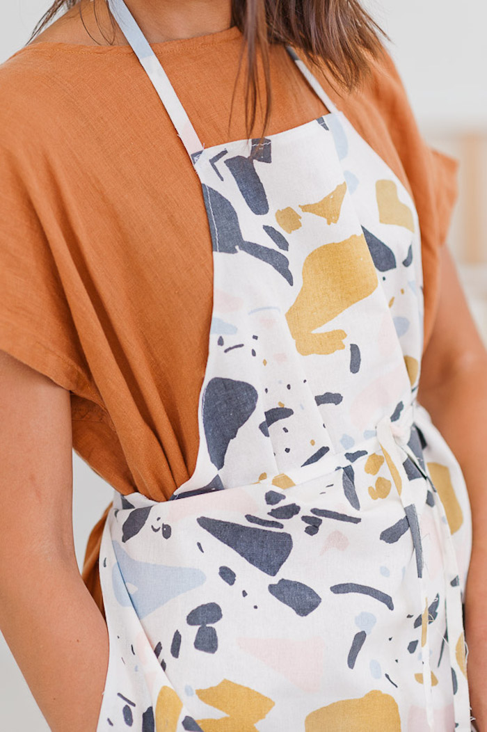 apron painted with abstract shapes, worn by women with brown hair, diy gift ideas, wearing orange dress