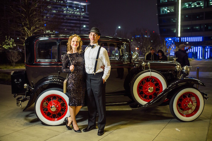 curly blonde woman, wearing a 1920s, art deco-inspired black dress, standing next to a man, in black trousers and white shirt, with suspenders and a bowtie, retro car in the background