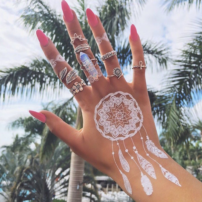 dreamcatcher-shaped, small henna tattoo, in pure white, on a hand with many different boho rings, and sharp pink nails