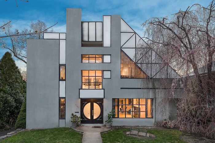 grey and off-white house, with lots of windows in different shapes and sizes, postmodern architecture, asymmetrical structure with geometrical motifs