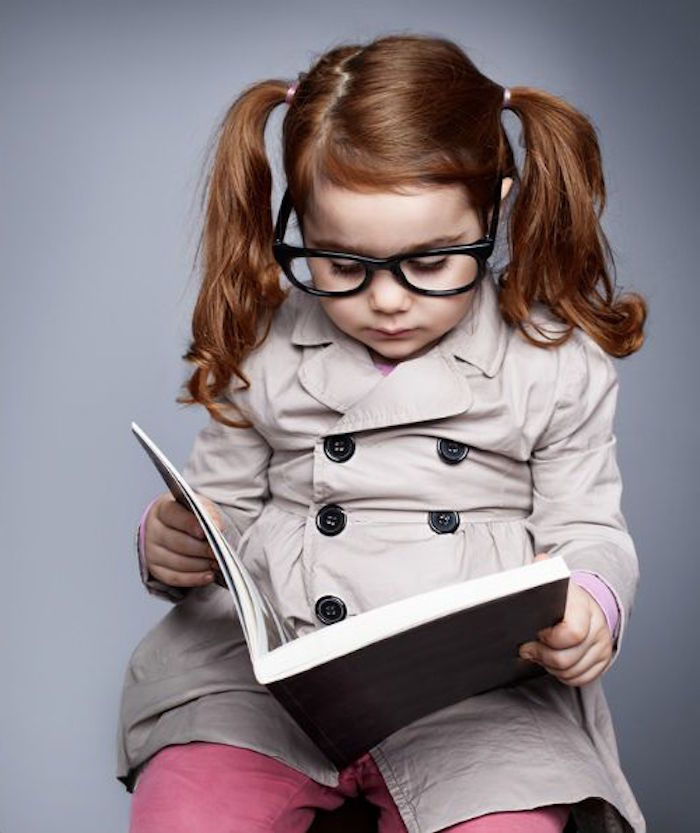 classic pigtails with a deep side part, simple hairstyles, on the auburn hair, of a small girl, with large glasses, holding an open book